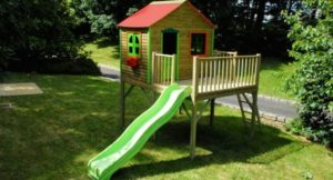 Bright-Kids-Play-Houses-By-Soulet-with-green-window-and-brown-wall-and-red-roof-and-garden-design-554x300